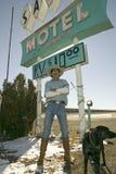 有狗立场的牛仔在沙子汽车旅馆符号前面 免版税库存照片