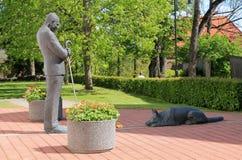 有狗雕塑的人 免版税库存图片