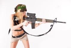 有狙击步枪的美丽的性感的白肤金发的妇女 免版税库存照片