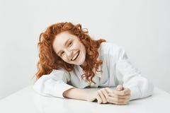 有狡猾的头发的愉快的相当女孩微笑看照相机坐对在白色背景的桌的 库存照片