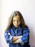 有狡猾神色的逗人喜爱的白肤金发的青少年的女孩 免版税库存图片