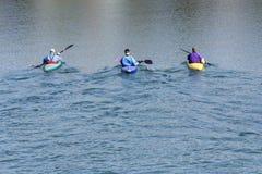 有独木舟的三名划船者 免版税库存图片