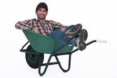 有独轮车的人。 库存照片