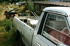 有独轮车的白色卡车在杂草 免版税库存图片