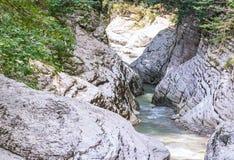 有狭窄的蓝色绿松石河用绿叶盖的一个灰色光滑的峡谷的运河的 免版税图库摄影