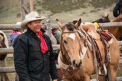 有猎枪、帽子和方巾的地道老西部牛仔在稳定的画象 免版税库存图片