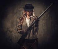 有猎枪和帽子的夫人从在黑暗的背景的狂放的西部 库存照片