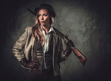 有猎枪和帽子的夫人从在黑暗的背景的狂放的西部 图库摄影