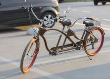 有猩红色轮子外缘的一辆纵排自行车在晚上太阳的一个停车场停放 库存图片