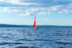 有猩红色风帆的风船做轮回旋反对树木繁茂的岸的背景 免版税库存照片