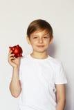 有猪存钱罐的白肤金发的男孩 免版税库存图片