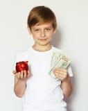 有猪存钱罐的白肤金发的男孩 图库摄影