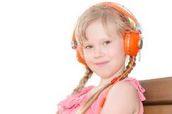 有猪尾听的语言课的女孩在耳机isol 图库摄影