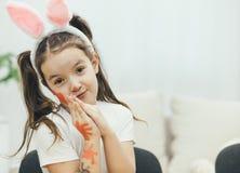 有猪尾和兔宝宝耳朵的可爱的女孩在她的头坐椅子,握逗人喜爱她的手 她的面孔和 库存照片