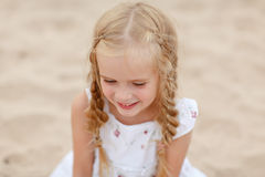 有猪尾和蓝色圆的眼睛的画象爱笑白肤金发的女孩 库存照片