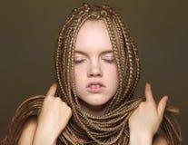 有猪尾和闭合的眼睛的美丽的白肤金发的年轻女人 免版税库存照片