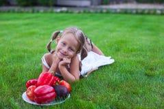 有猪尾的可爱的女孩在有板材的一个庭院里 免版税图库摄影