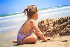 有猪尾的后侧方视图小女孩坐沙子海滩 库存图片