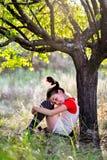 有猪尾的哀伤的女孩在树下 库存图片