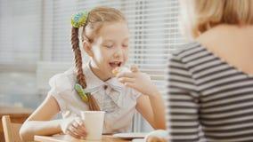 有猪尾的女孩吃与她的妈咪的蛋糕咖啡馆的 免版税库存图片