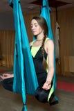 有猪尾的女孩执行锻炼飞行瑜伽 图库摄影