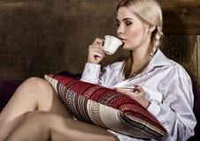 有猪尾的少妇在人在他的赤裸身体、饮用的咖啡或者茶的` s衬衣坐沙发 免版税图库摄影