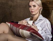 有猪尾的少妇在人在他的赤裸身体、饮用的咖啡或者茶的` s衬衣坐沙发 免版税库存照片