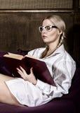 有猪尾的少妇在人在他的赤裸身体的` s衬衣,读书坐沙发 免版税库存照片