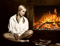 有猪尾的少妇在人在他的赤裸身体的` s衬衣,读书由壁炉 库存图片