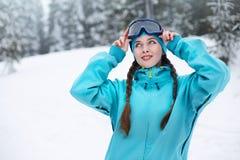 有猪尾的微笑的北欧妇女在防护滑雪风镜投入 接触面具的挡雪板女孩在滑雪场  免版税库存图片