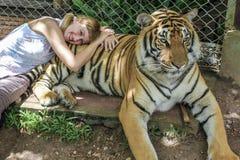 有猪尾的白肤金发的女孩在泰国一只勇敢的老虎躺下 免版税图库摄影