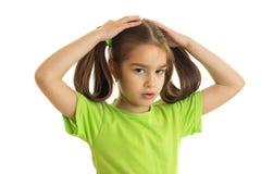 有猪尾的逗人喜爱的小女孩在绿色衬衣 库存照片