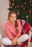 有猪尾的青少年的女孩在一件红色格子花呢上衣 免版税库存图片