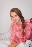 有猪尾的青少年的女孩在一件红色格子花呢上衣 库存照片