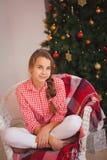 有猪尾的青少年的女孩在一件红色格子花呢上衣 库存图片