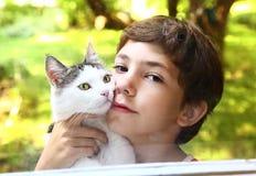 有猫关闭的青春期前的英俊的男孩照片 图库摄影
