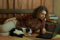 有猫和膝上型计算机的女孩 库存图片