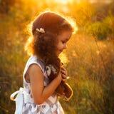 有猫头鹰玩具的可爱的微笑的女孩在公园 平衡晴朗 方形的照片 免版税库存图片