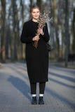 有猫杨柳花束的穿黑外套漫步在甚而的年轻愉快的美丽的妇女全长情感画象  库存图片