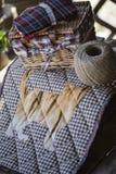 有猫的手工制造被子毯子在与麻线和缝合的工具的木桌上 免版税图库摄影