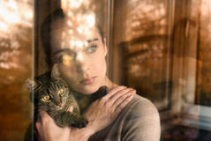 有猫的美丽的妇女和由窗口坐 免版税库存图片