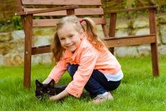 有猫的逗人喜爱的小女孩 免版税库存图片
