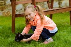 有猫的逗人喜爱的小女孩 免版税图库摄影
