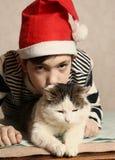 有猫的青少年的男孩在圣诞节圣诞老人帽子 免版税库存照片