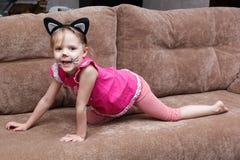 有猫面孔绘画的小女孩在长沙发 免版税库存图片