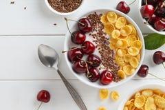 有玉米片、酸奶和甜樱桃的滋补夏天早餐碗在白色木桌上 库存图片