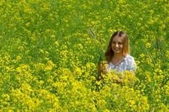 有玉米穗的美丽的女孩在花田的 图库摄影