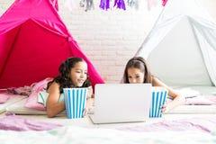 有玉米花桶的女孩观看在膝上型计算机的电影在帐篷 图库摄影