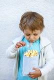 有玉米花袋子的愉快的小男孩 免版税库存照片