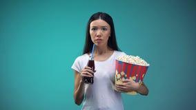 有玉米花观看可怕电影和喝泡沫腾涌的水的杯子的震惊妇女 股票视频
